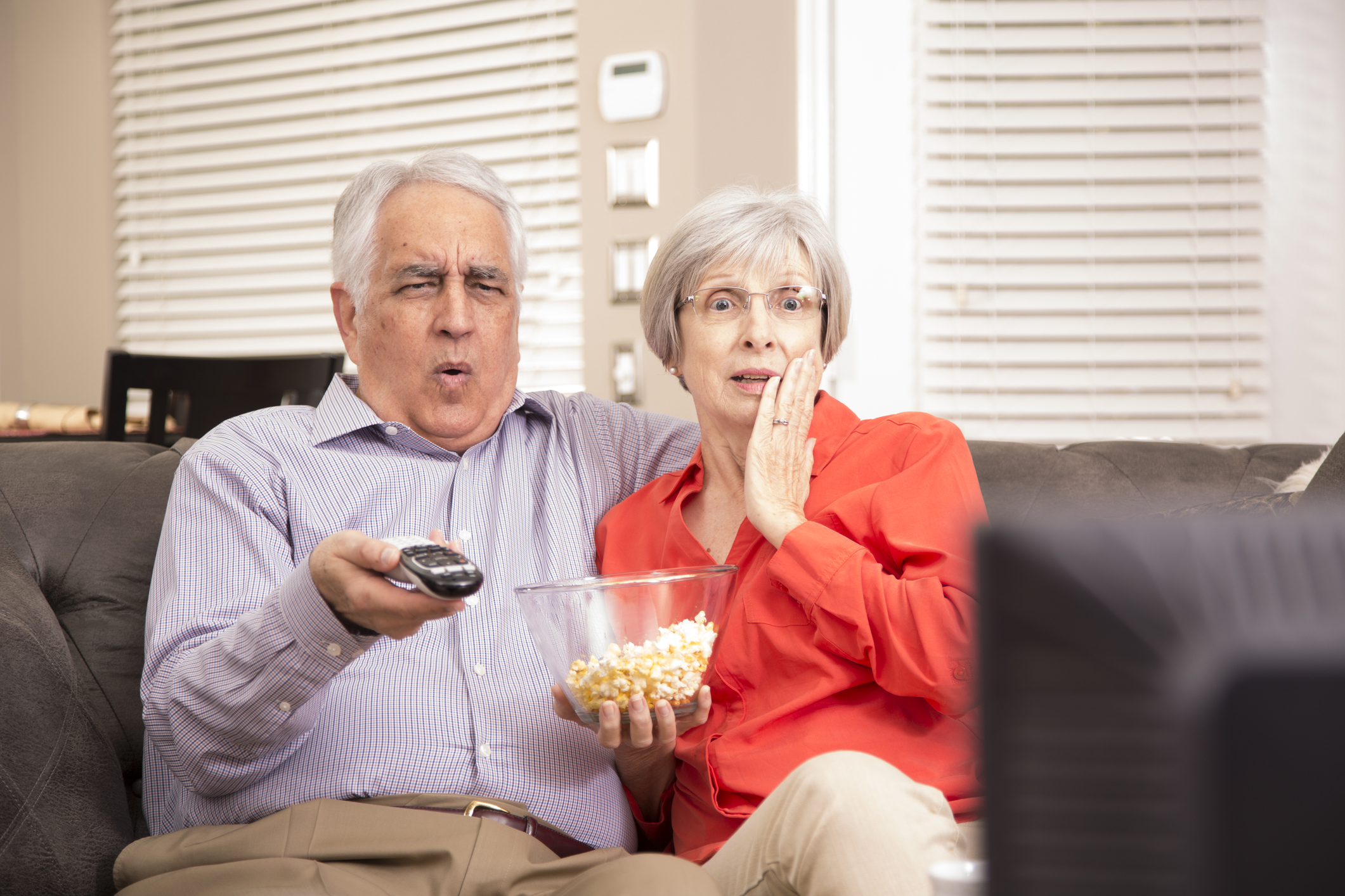 Senior adult couple at home watching television together.