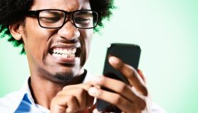 Young afro-haired nerd grimaces at cellphone he holds