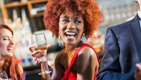 Young black woman in bar drinking, laughing