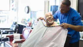 Black barber tying apron on customer in retro barbershop