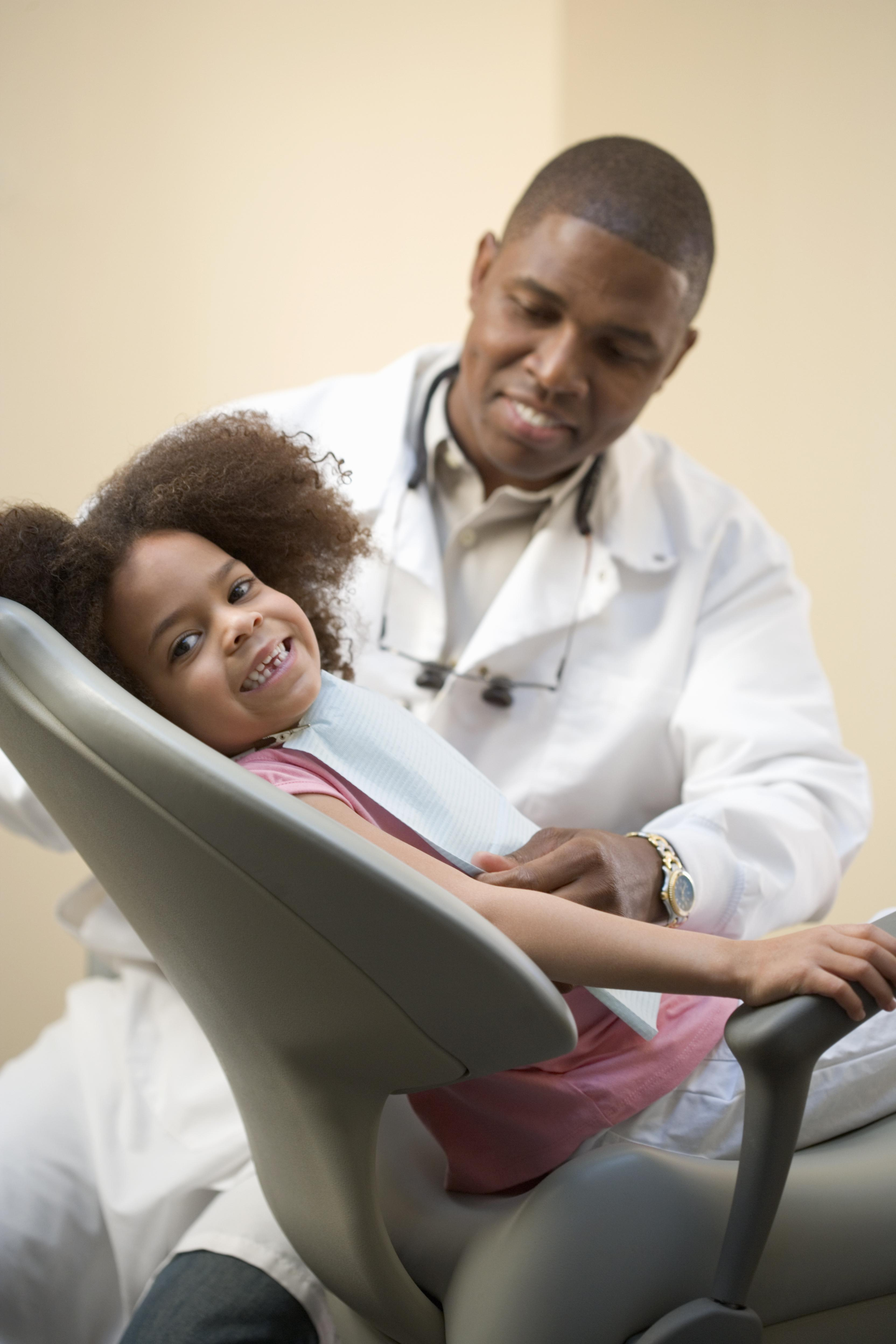 Girl (4-6) sitting in dental chair with dentist