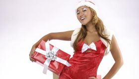 Smiling young woman with Christmas gifts Isolated on white background