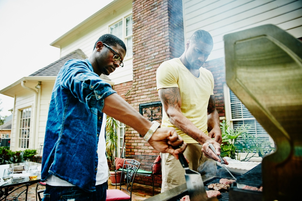 Friends barbecuing during backyard party