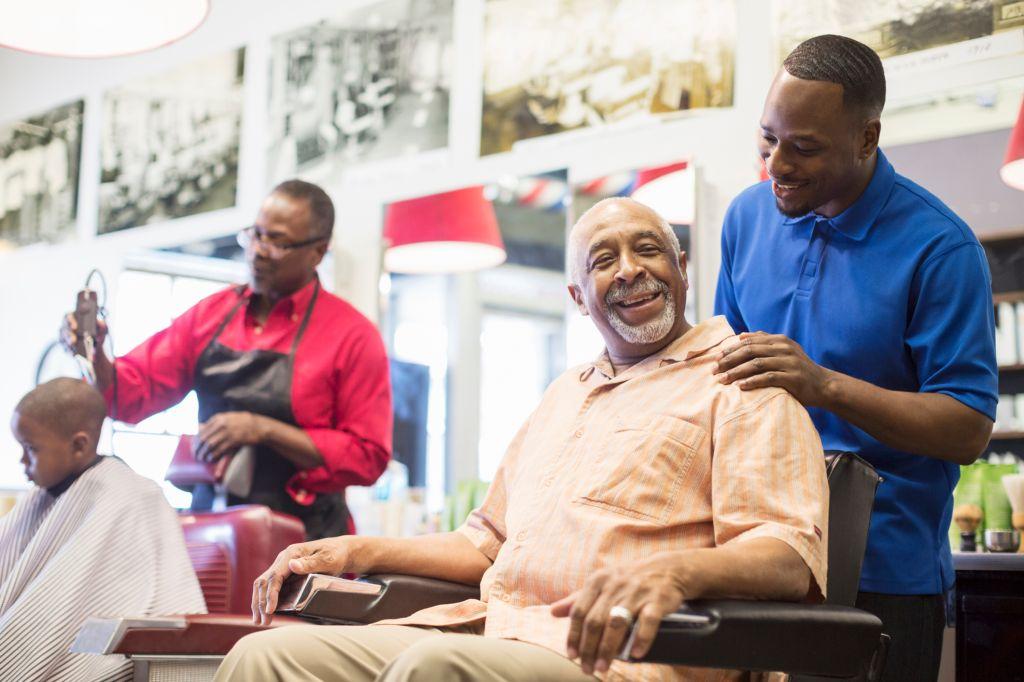 Black barber talking to customer in retro barbershop