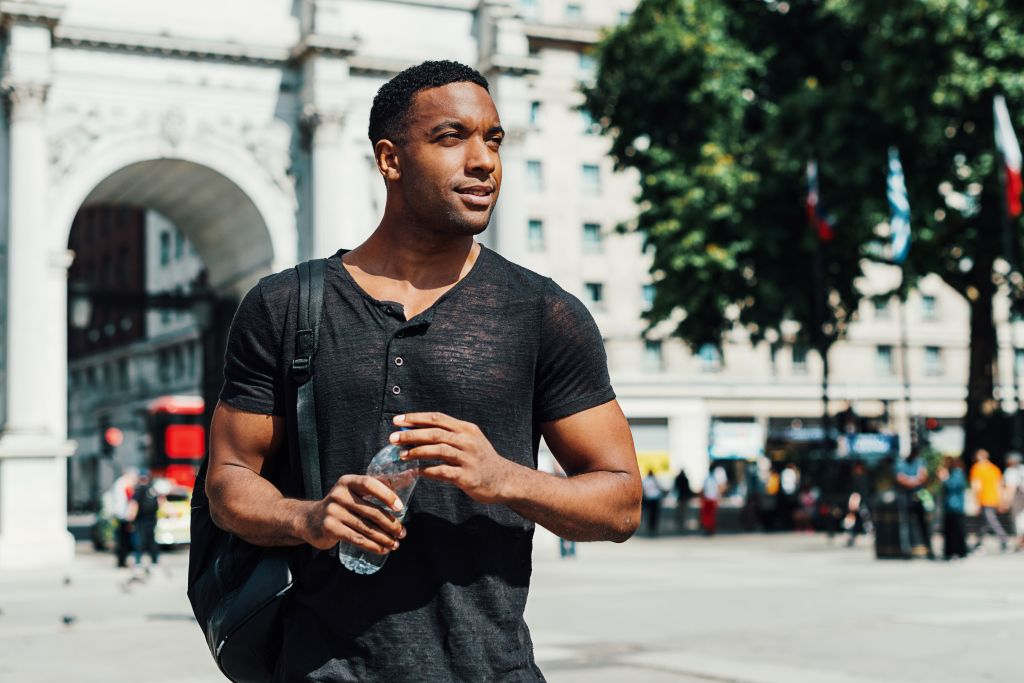 Afro-Caribbean guy in London with bottle of water
