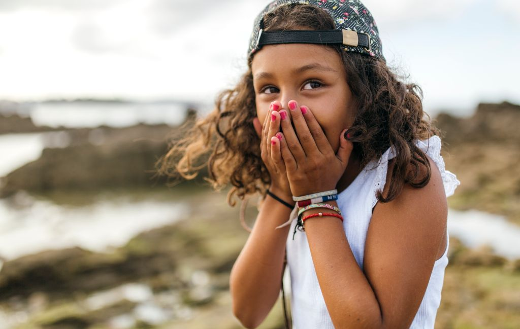 Spain, Gijon, portrait of little girl covering mouth with her hands