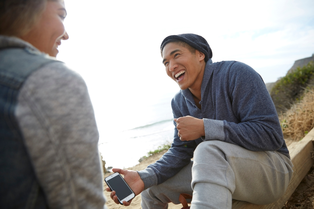 Man with smartphone laughing with friend by coast