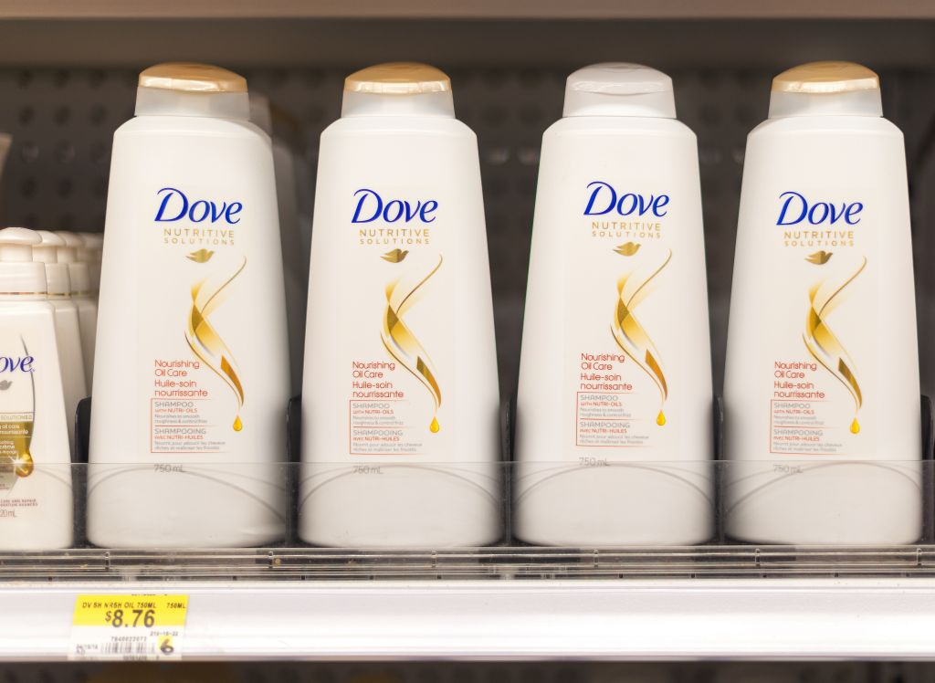 Dove shampoo and conditioner bottles in a shelf. Dove is one...