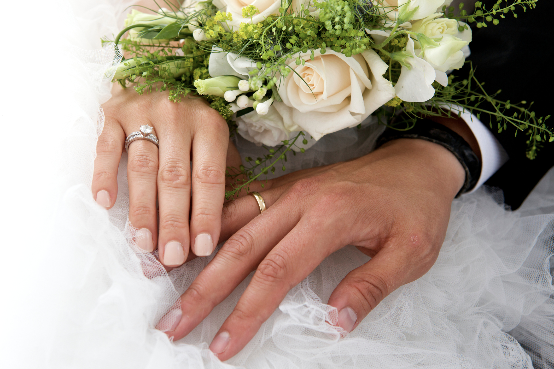 Close-Up Of Newlywed Couple Holding Rose Bouquet