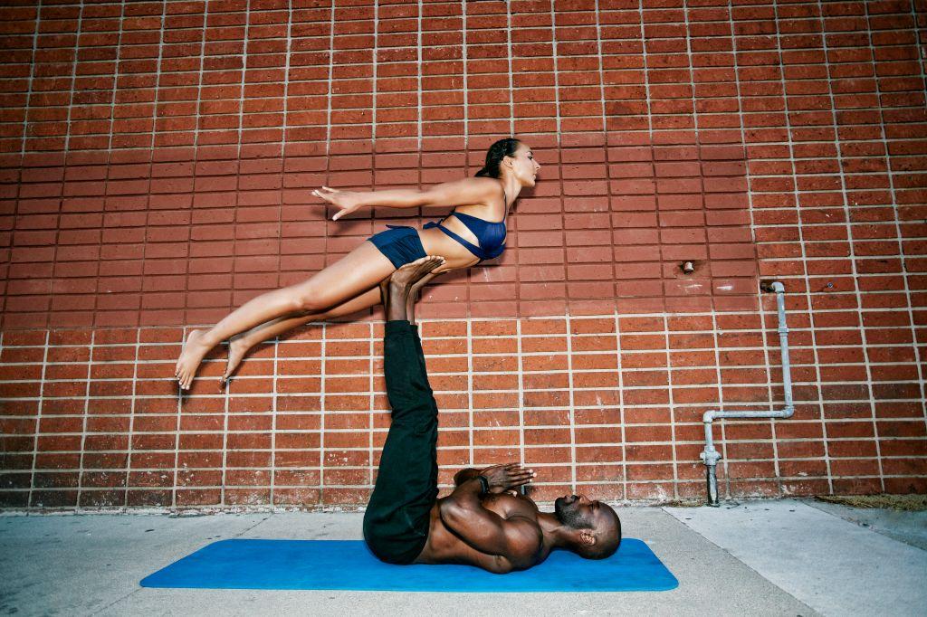Couple performing acro yoga on sidewalk near brick wall