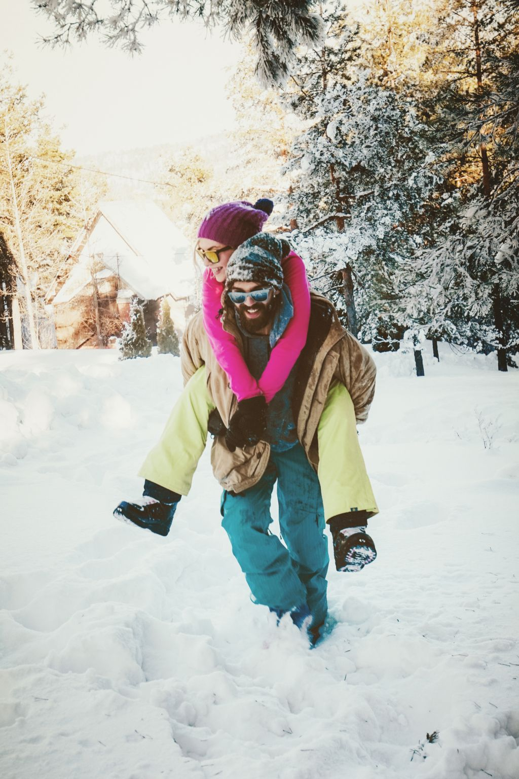 Man walking through deep snow with woman on his back