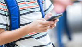 Schoolboy uses smart phone while waiting for bus