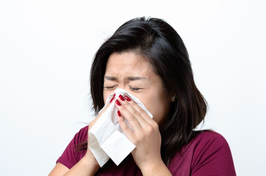 Young Woman Sneezing Against White Background