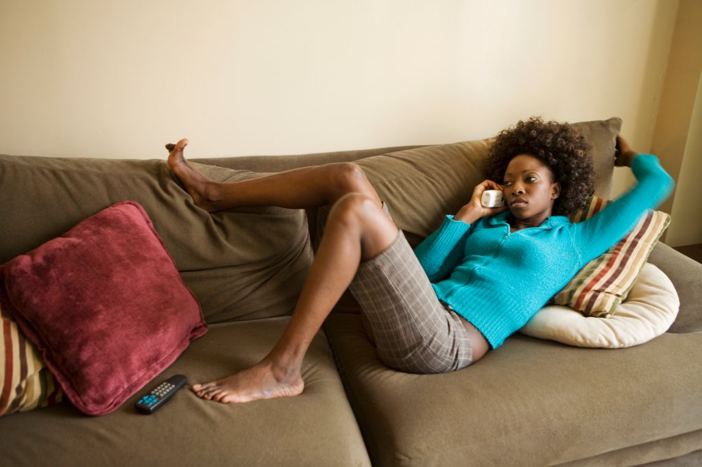Young woman lying on couch, talking on telephone