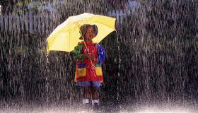 Boy (4-6) wearing raincoat, standing under umbrella in rain