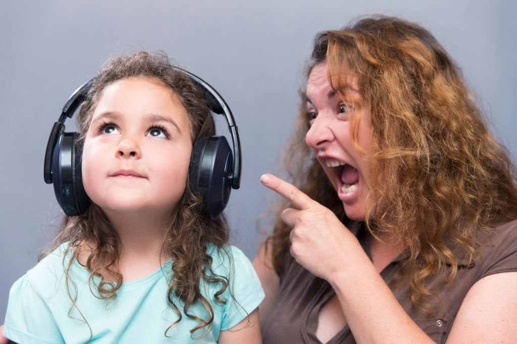 Angry Mother Shouting While Cute Girl Listening To Headphones Against Gray Background
