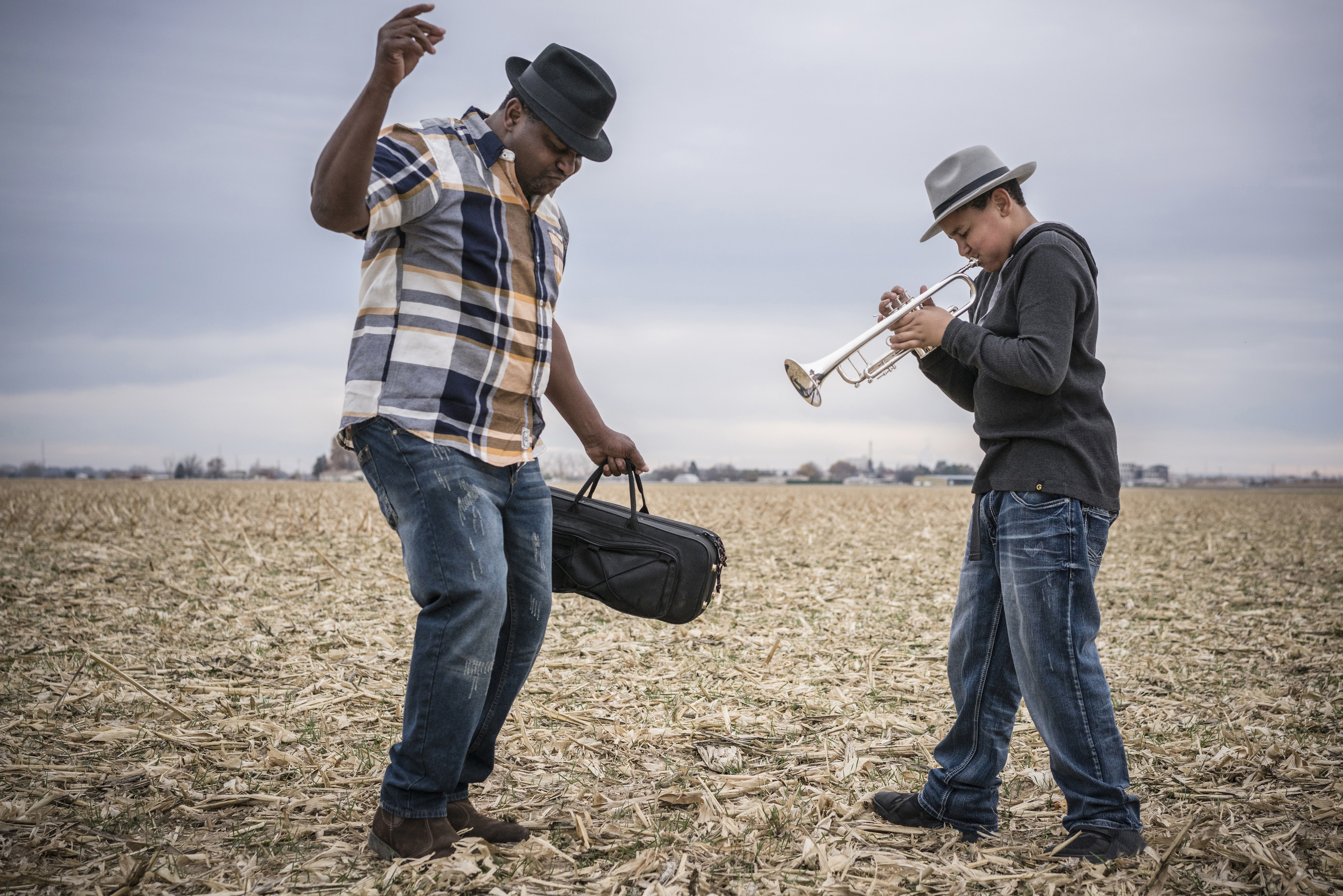 Father dancing to son playing trumpet in field