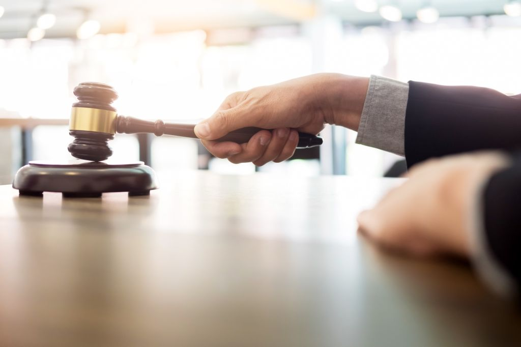 Cropped Hands Of Man Holding Gavel At Table