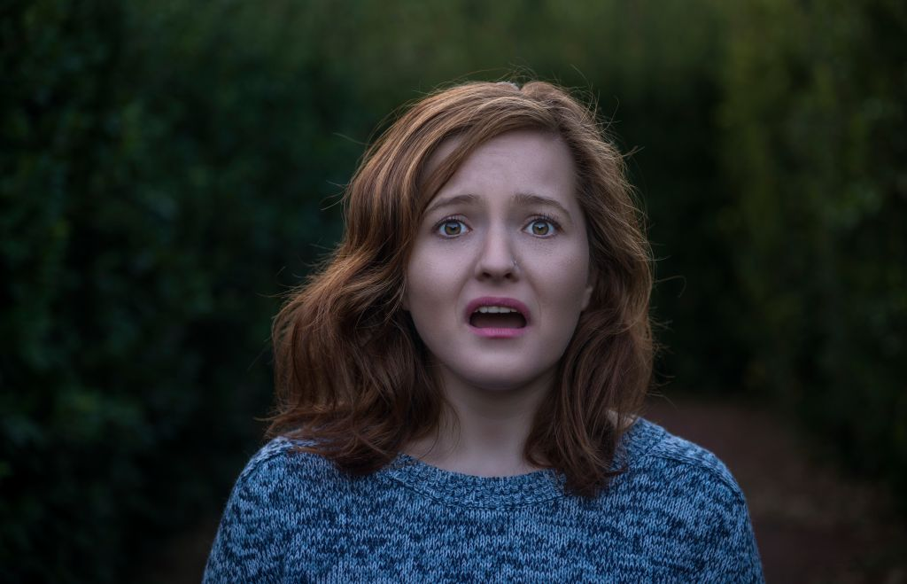 Portrait of shocked young woman looking at camera with negative facial expression