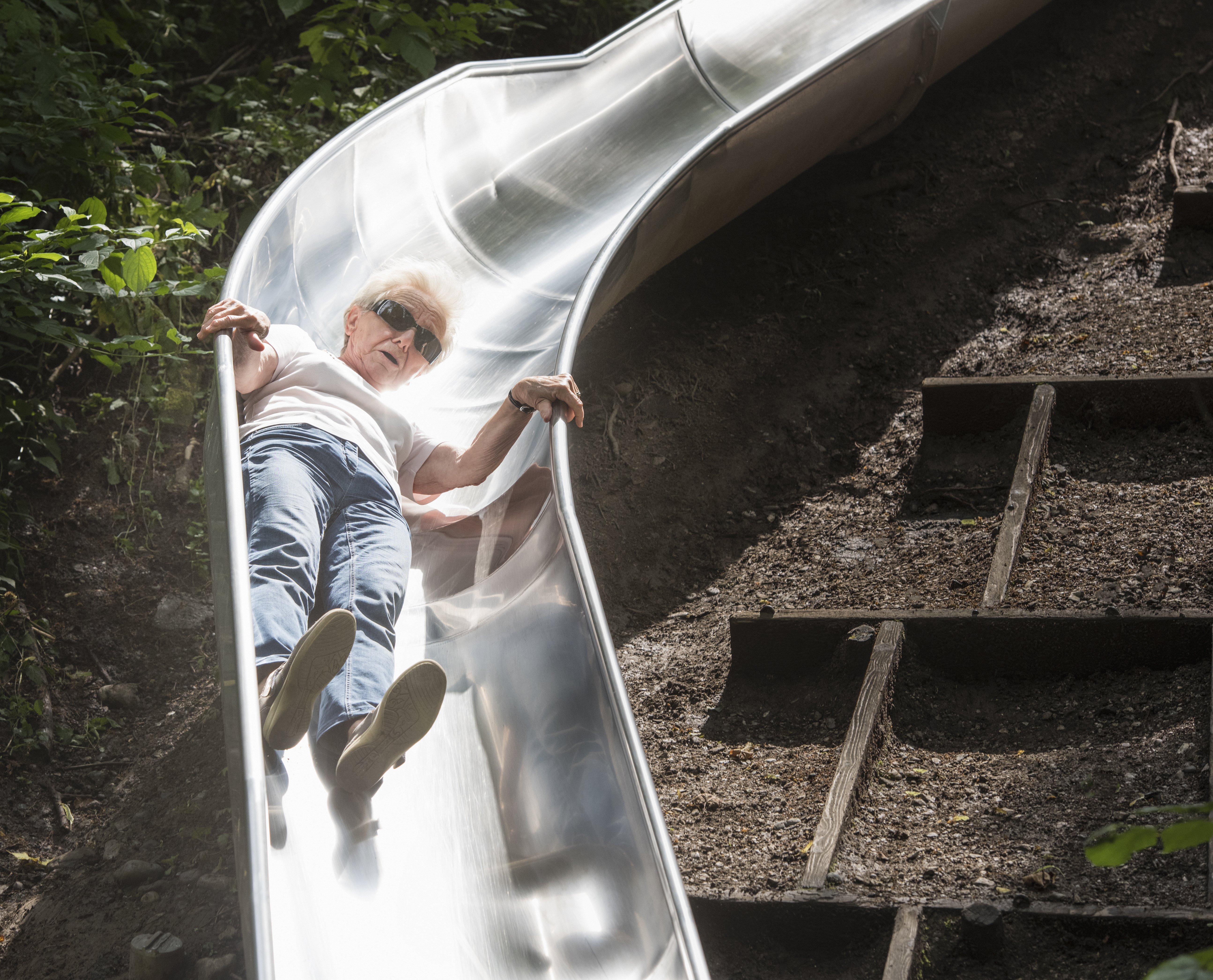 Woman sliding down playground slide