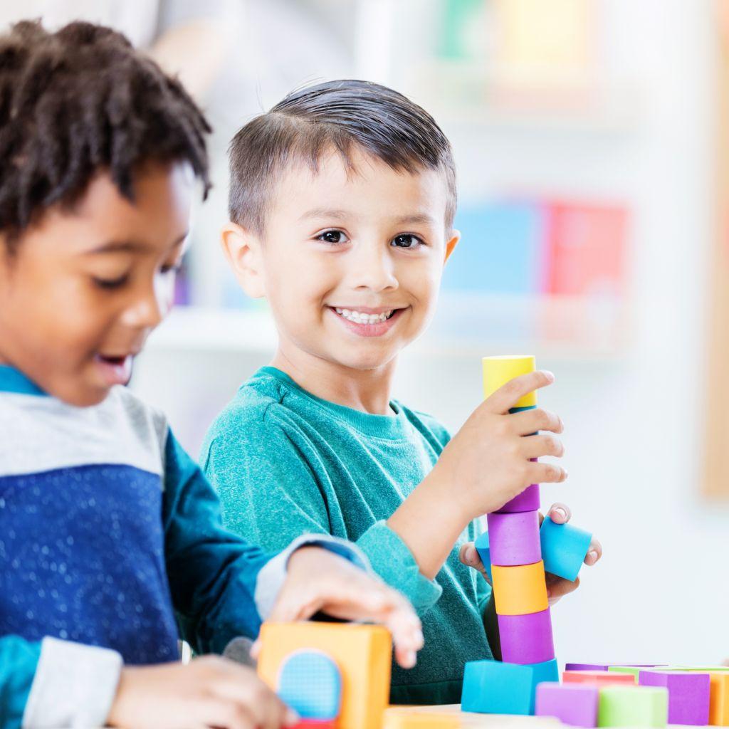 Playful kindergarten student plays with building blocks