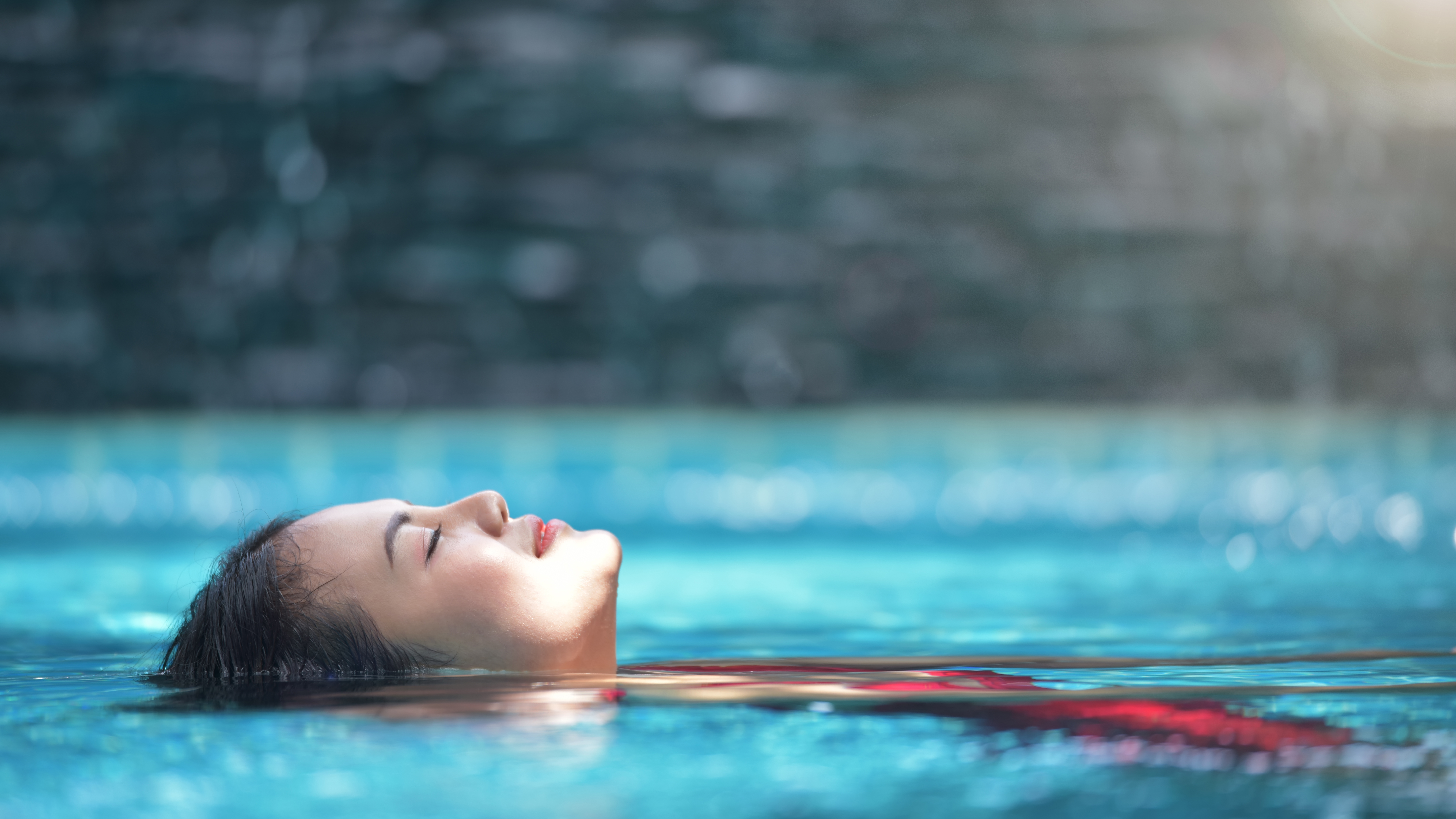 Close up view of an attractive young woman relaxing on a spa's swimming pool on top of roof deck building . Travel, happiness emotion, summer holiday concept .