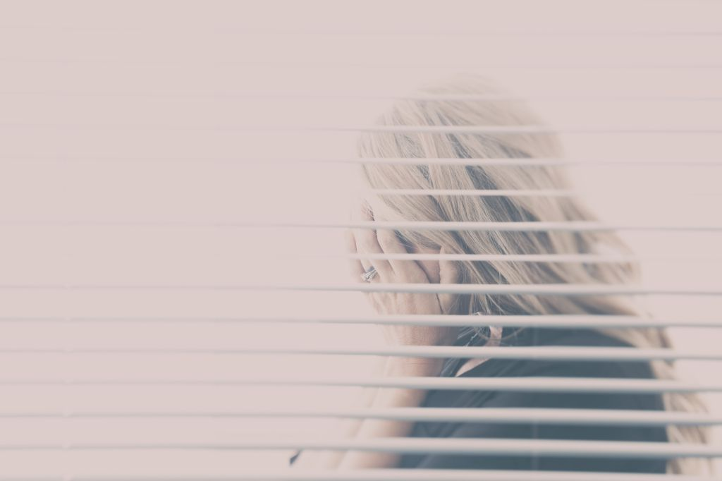 Woman With Blond Hair Seen Hiding Her Face Through A Window With Blinds