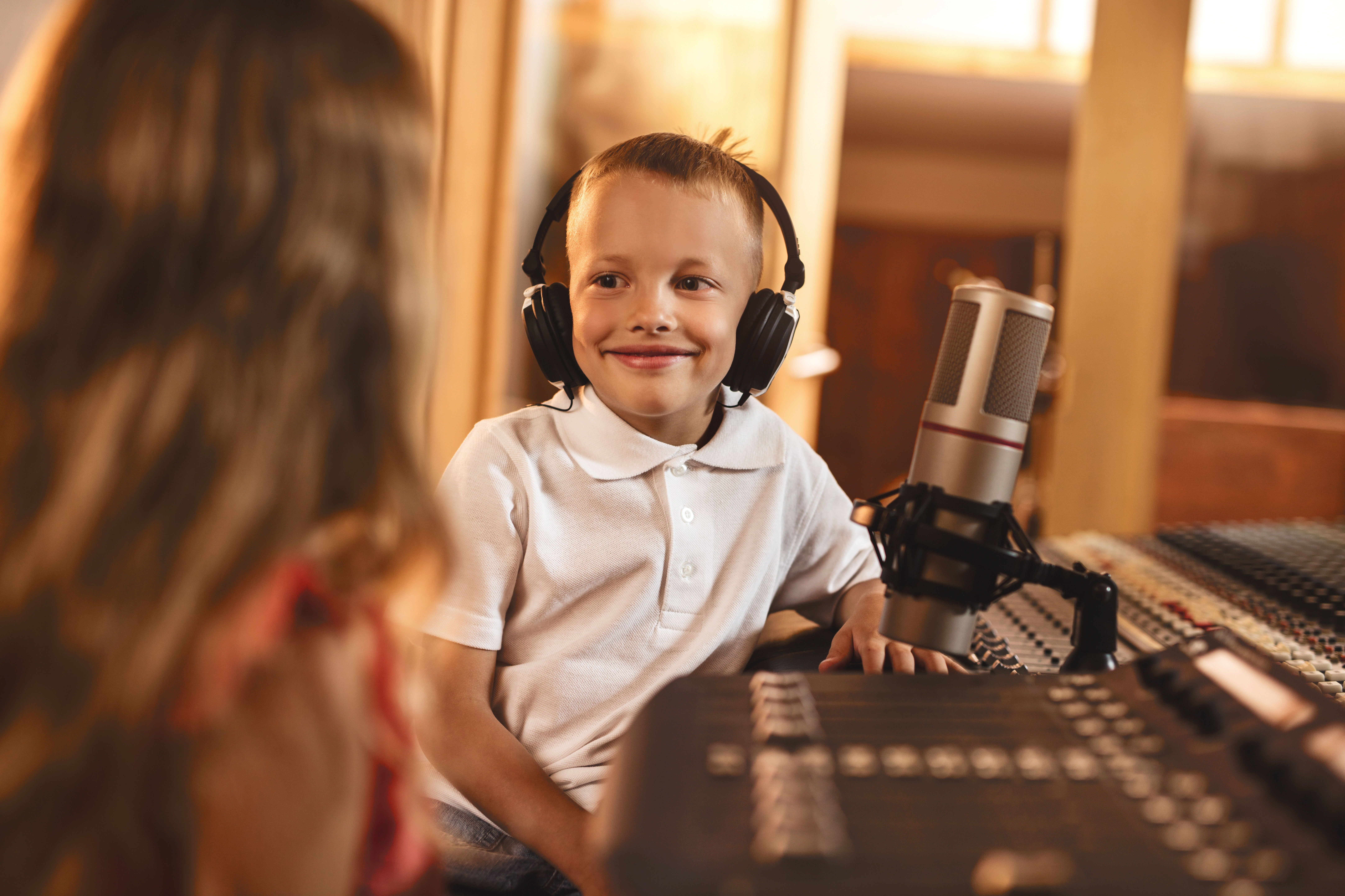 Happy little commentator having a guest in a radio station during live broadcast.