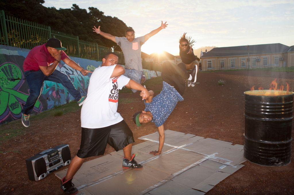 Group of five men breakdancing in park at dusk