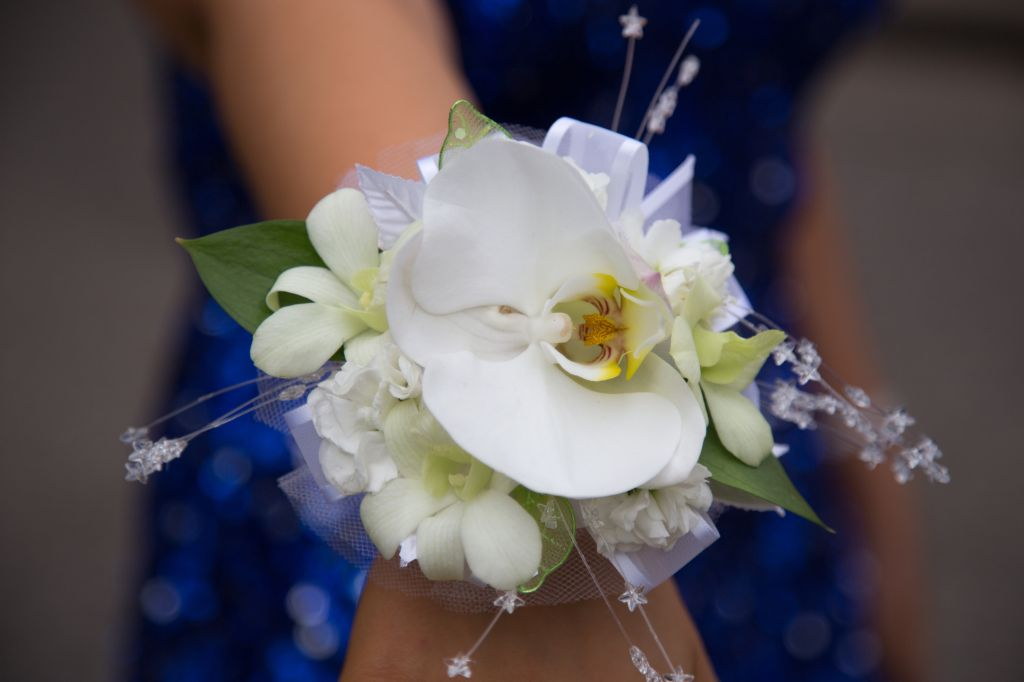 Close up of girl in sparkly blue dress wearing white flower corsage on wrist before prom