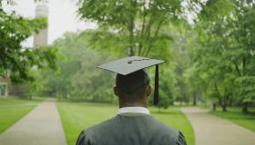 Male college student wearing cap and gown, rear view
