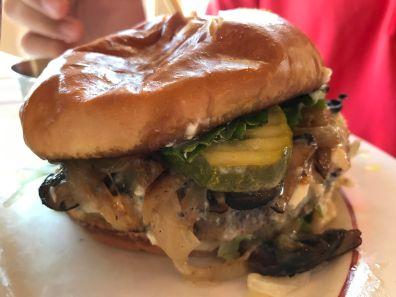 Close up of a hamburger with bun, lettuce, cheese and garnish