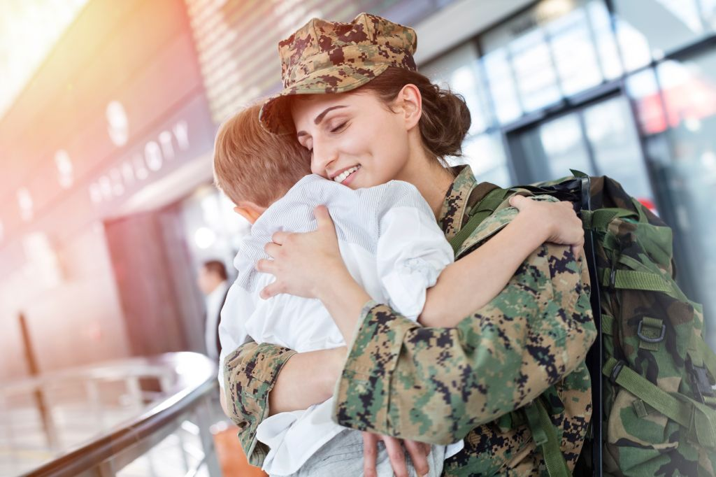 Son greeting and hugging soldier mom at airport