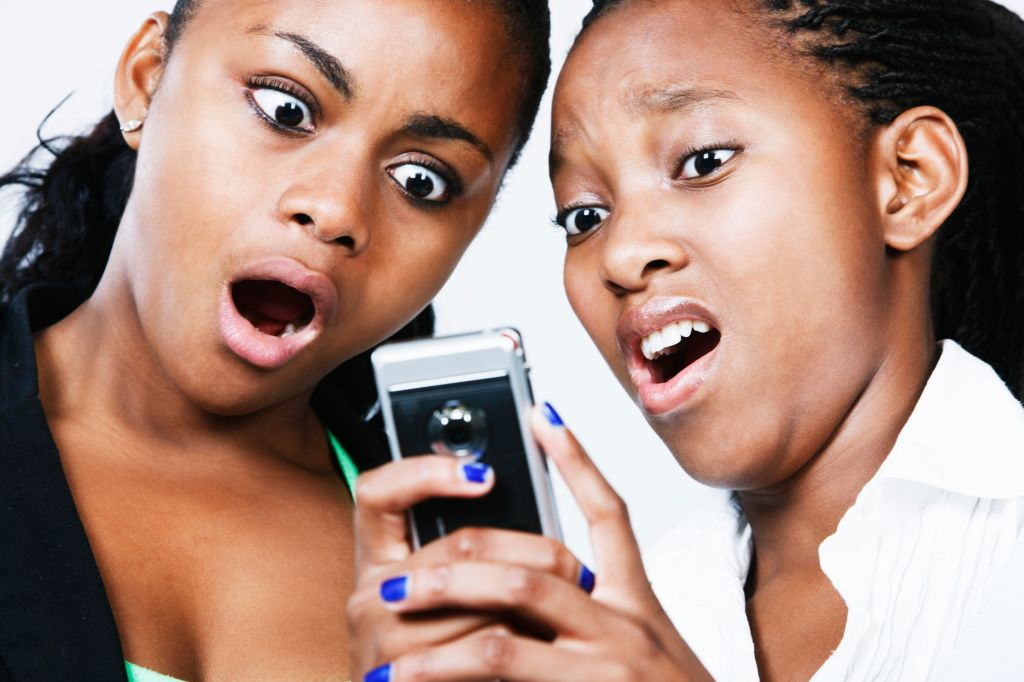 Two young women look down, horrified, at mobile phone
