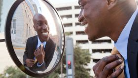 African American businessman adjusting tie in mirror