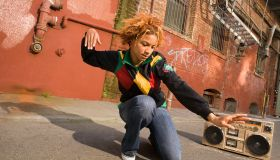 Young woman kneeling on street, dancing to stereo, low angle view