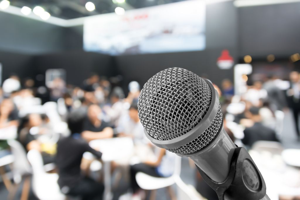 Microphone with blurred photo of conference hall or seminar room with attendee background, Business meeting concept.