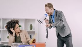 Business man screaming with megaphone at frustrated female coworker
