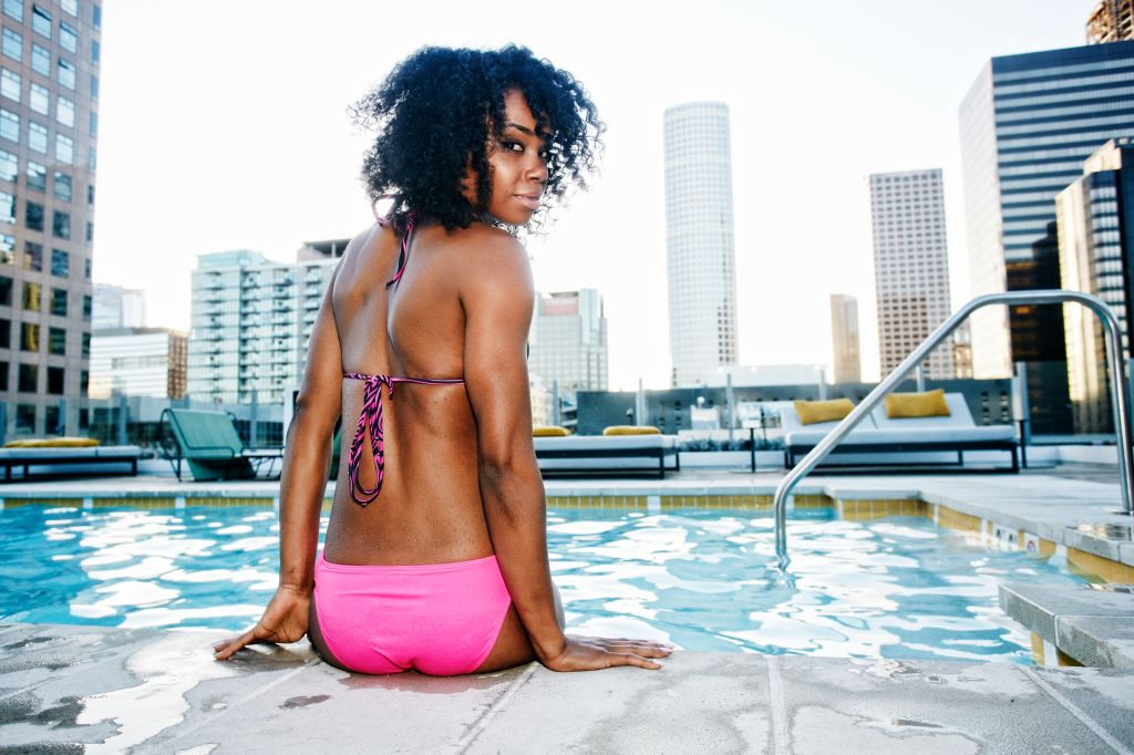 Black woman sitting poolside looking over shoulder