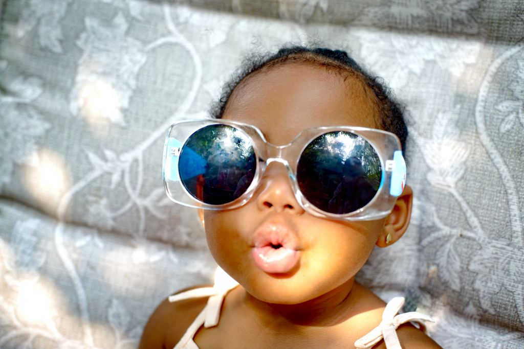 Baby girl sitting on lounge chair wearing sunglasses, portrait