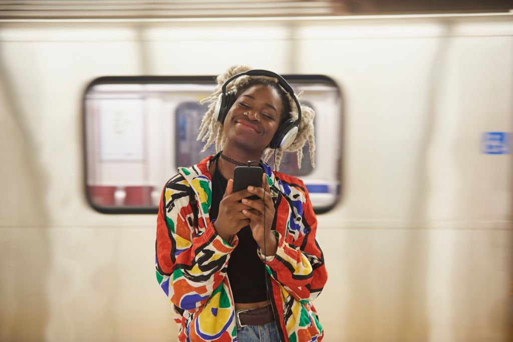 Black woman listening to cell phone with headphones near subway