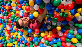 young man falling into a ball pool