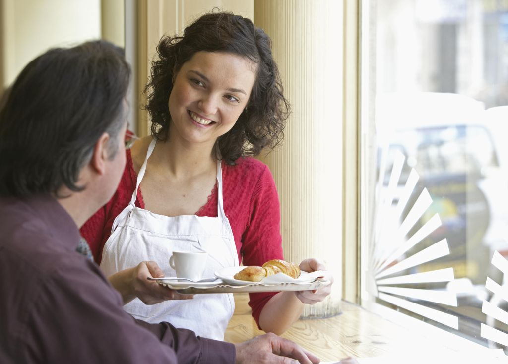 Young waitress serving client in cafe, smiling