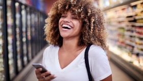 Black woman holding cell phone laughing in grocery store