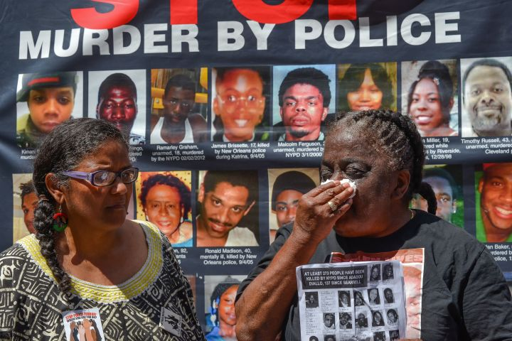 Juanita Young (right) tries a tear from her eye while...