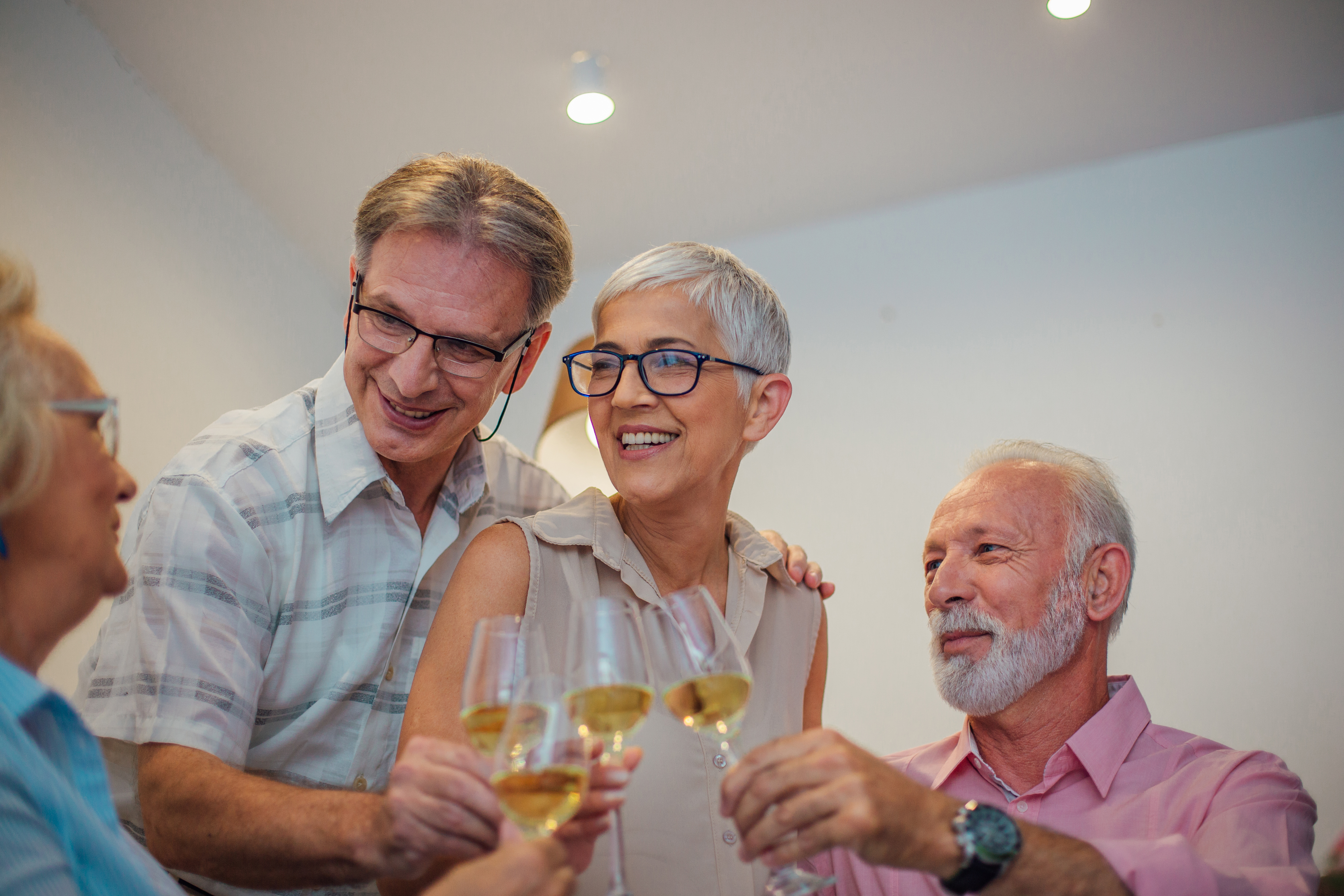 Senior couple hugging and having celebratory toast with friends