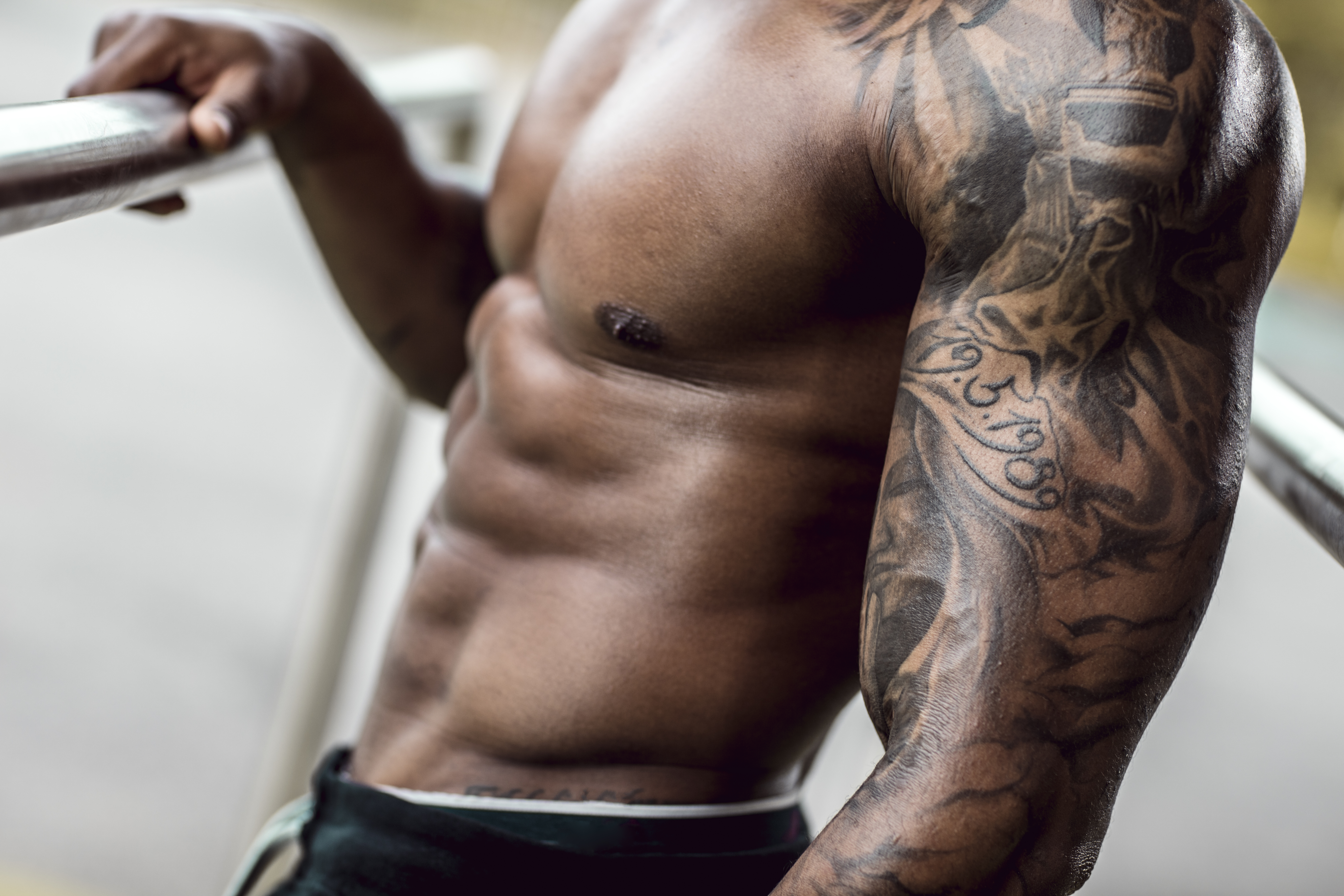 Tattooed biceps of physical athlete, close-up