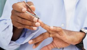 African American man clipping fingernails