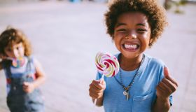 Multi-ethnic children with colorful lollipops outdoors on summer vacations