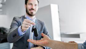 Car salesman making a sale in office delivering car key